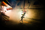 The Festival of the Magdelena is a two day annual party, which takes place in the neighborhood of Mixiuhca de la Magdelena in Mexico City.  Here a neighbor sprints down a narrow street, trying to keep ahead of his exploding headwear, on July 28, 2008.