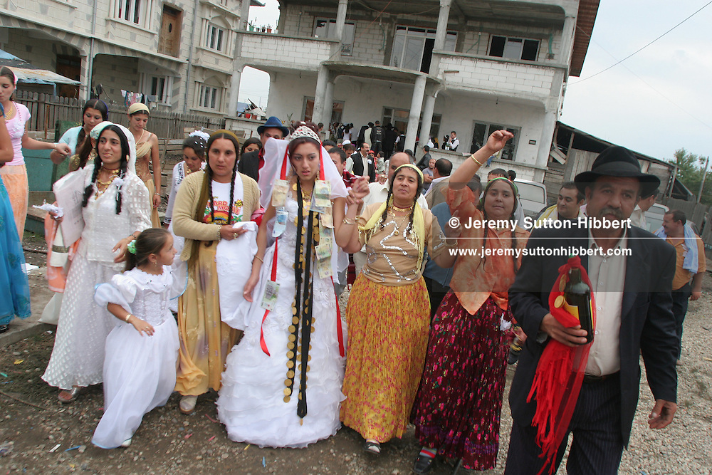 Garoafa Mihai (in wedding dress, centre), aged 14, is taken from her family home by her husband-to-be's family during the celebrations of her wedding to 13 year old Florin 'Ciprian' Lulu (not pictured), in Sintesti, Romania, on Sunday, Sept. 24th 2006. Both garoafa and Ciprian are Roma (gypsies) from the village of Sintesti, 15 kilometres from Bucharest, Romania. Their partnership was decided by their parents and not through love, and under Romanian law is illegal. The children will neither complete legal paperwork for the wedding, nor visit the local Romanian Orthodox church for a blessing. On her wedding day Garoafa wore approximately 30-40,000 USD of gold Franz Josef coins on her dress, part of the large dowry that she takes with her as she begins her married life. For the guests and for the people of the village another 30,000 USD of pigs were killed to be eaten and given away as presents of food. Another 30,000 USD was spent on famous Roma musicians to come and sing 'manele'  type music at the wedding extolling the wealth and status of their patrons for the weekend in their songs.
