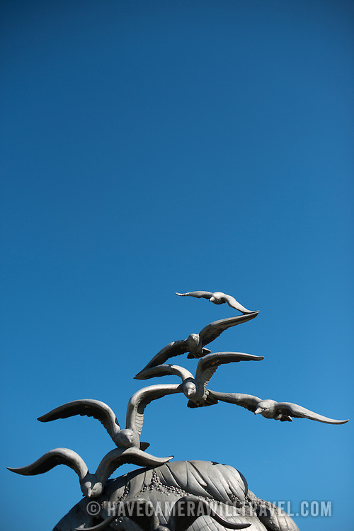 A clear blue sky with the seagulls on top of the Navy-Merchant Marine Memorial in Arlington, Virginia, on Columbia Island on the banks of the Potomac across from Washington DC. The memorial honors those who lost their life at sea in World War I and was dedicated in 1934. The main sculpture is cast from aluminum.