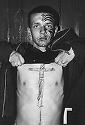Skinhead with facial tattoo lifting up his top to reveal a 'skinhead on the cross' tattoo on his chest