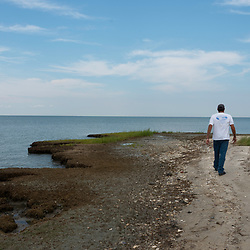 August 4, 2017 - Tangier Island, VA - <br /> Mayor James &quot;Ooker&quot; Eskridge tours &quot;The Uppards,&quot; a previously habited portion of Tangier Island that is today very diminished in size due to erosion.  A few of the old homes from this area of the island have been moved to the more inhabited part of the island, across a widening waterway once accessible by bridge. That bridge no longer exists. .  Photo by Susana Raab/Institute