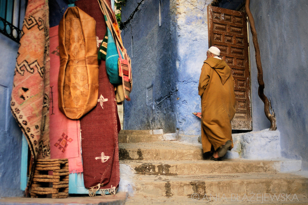 Morocco, Chefchaouen. Man in the jellaba climbing the stairs in the blue medina.