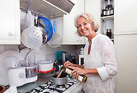 Portrait of senior woman adding olive oil to saucepan at kitchen counter