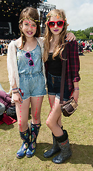 © Licensed to London News Pictures. 13/06/2015. Isle of Wight, UK.  Two girls in stylish festival wear pose in the warm afternoon sun while Nothing but Thieves perform at Isle of Wight Festival 2015 on Saturday Day 3 in the warm afternoon sun.  Yesterday suffered torrential rain all afternoon and evening, after a first day of warm sun.  This years festival include headline artists the Prodigy, Blur and Fleetwood Mac.  Photo credit : Richard Isaac/LNP