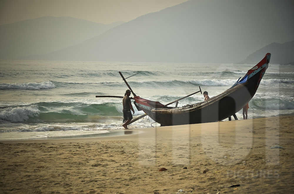 Fishermen come back after fishing and push their boat up on the beach in Lang Co, Centre Vietnam, Asia