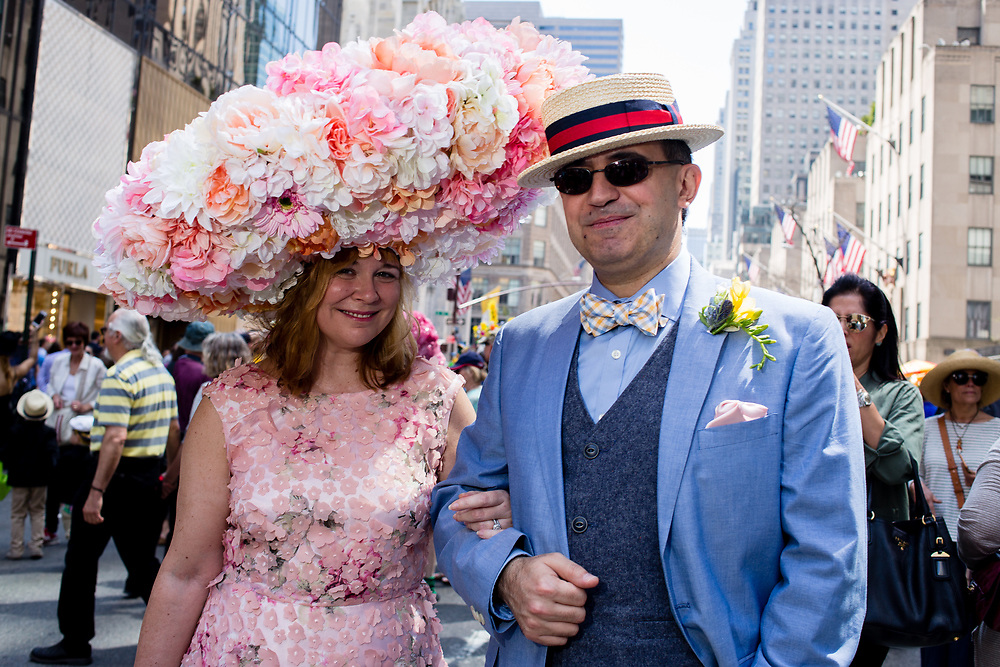 New York, NY - April 16, 2017.  A man and a woman at New York's annual Easter Bonnet Parade and Festival on Fifth Avenue. The Woman wears a hat that appears to be 3 feet across, and is completely covered in flowers.