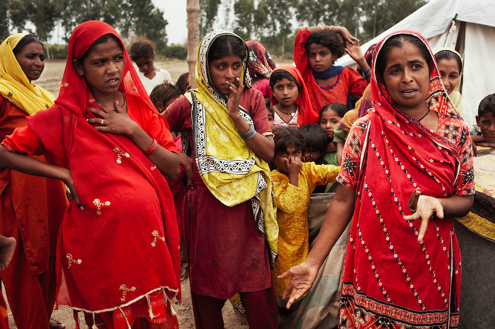 Pregnant women (from right; Nahida, 22 years old is 9 months pregnant, Zohra, 20 years old is 9 months pregnant, Froze, 25 years old is 5 months pregnant and has 3 children) talk about their experience of maternal health during the recent floods in a temporary shelter near the village of Geo Kaloid in Mirpur Khas district, Sindh, Pakistan on November 3, 2011. In August 2011, Heavy monsoon rains triggered flooding in lower parts of Sindh and northern parts of Punjab.