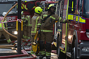 "Fire fighters attend a fire in premises on the Walworth Road, on 16th January 2019, in London, England. According to London Fire Brigade, ""Ten fire engines and around 70 firefighters were called to a fire at a shop with flats above on Walworth Road in Walworth. The ground floor of the building was destroyed by the blaze and a small part of the basement, first floor and second floor were also damaged. Firefighters wearing breathing apparatus rescued one man and one woman from a first floor flat roof using a short extension ladder. The woman was treated at the scene for smoke inhalation then taken to hospital by London Ambulance Service crews."""