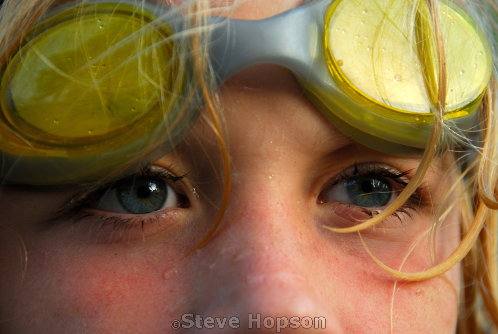 A young swimmer and his goggles just out of the water on a sunny day in Austin Texas, June 2, 2007.