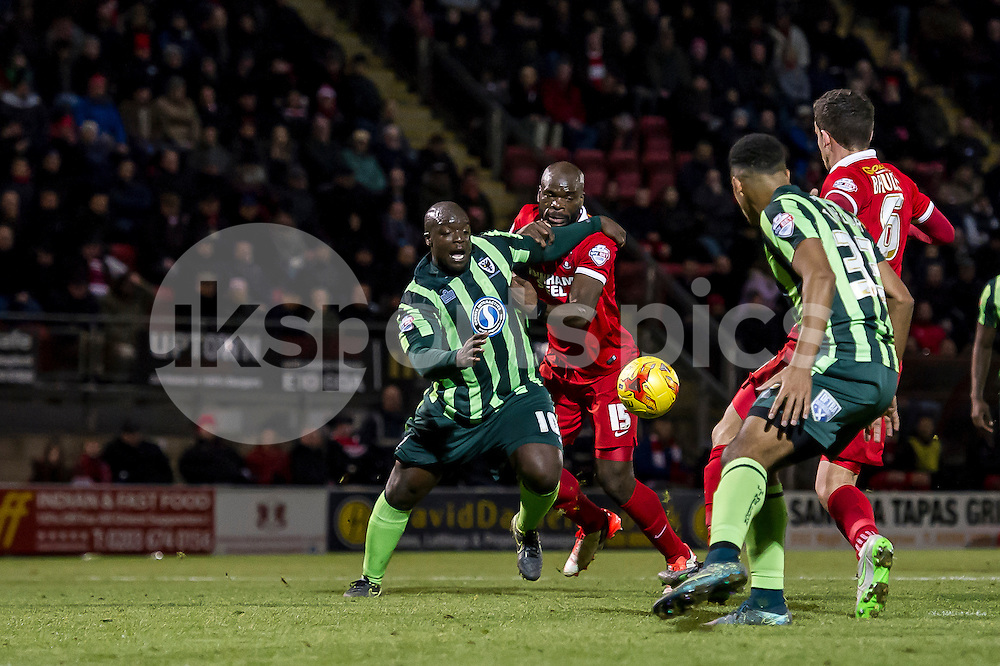 Adebayo Akinfenwa of Wimbledon and  of Leyton Orient challenge for the ball during the Sky Bet League 2 match between Leyton Orient and AFC Wimbledon at the Matchroom Stadium, London, England on 28 November 2015. Photo by Salvio Calabrese.