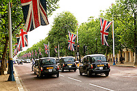 A horizontal photo of Cabs and Union Jack flags along The Mall, London, England.