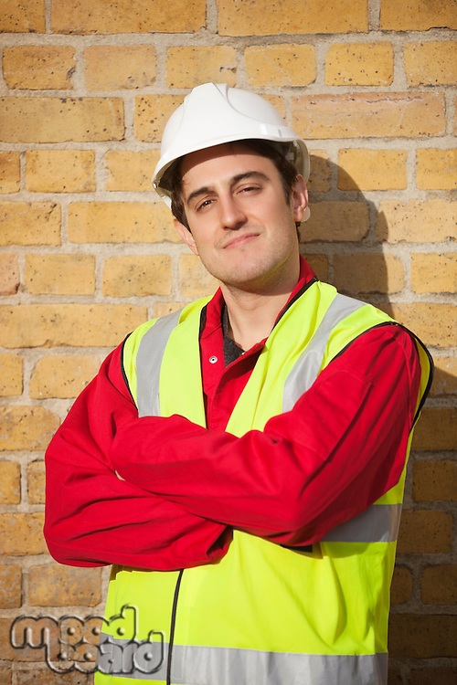 Portrait of young man wearing safety vest and hardhat against brick wall