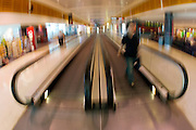 Commuter on an airport moving walkway, Australia