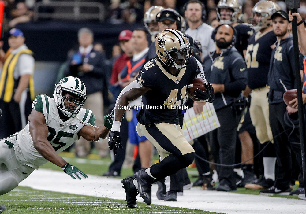 Dec 17, 2017; New Orleans, LA, USA; New Orleans Saints running back Alvin Kamara (41) breaks a tackle attempt by New York Jets outside linebacker Josh Martin (95) during the first quarter at the Mercedes-Benz Superdome. Mandatory Credit: Derick E. Hingle-USA TODAY Sports