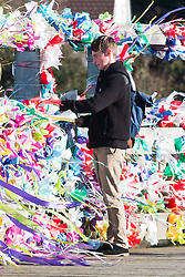 © Licensed to London News Pictures. 22/11/2015. Shoreham By Sea, UK. A young man lays flowers at the toll bridge where hundreds of coloured ribbons fly in the wind as a remembrance service is being held in Lancing College chapel for the families of the victims of the Shoreham Airshow Plane crash.Photo credit : Hugo Michiels/LNP