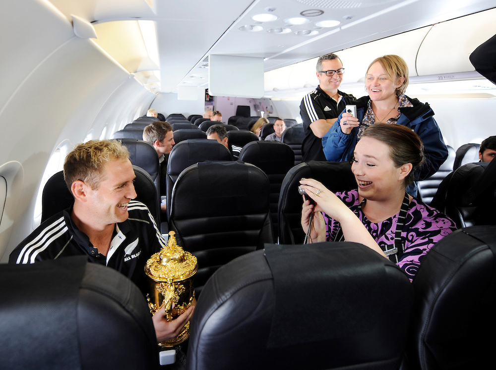 New Zealand's  Andy Ellis is photographed with the Rugby World cup by Air New Zealand stewardess Katie McDonald during the flight to Christchurch, New Zealand, Tuesday, October 25, 2011. Credit:SNPA / Ross Land