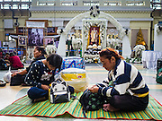 "03 JANUARY 2017 - BANGKOK, THAILAND: Travelers sit on the floor in front of a portrait of Bhumibol Adulyadej, the Late King of Thailand, in Hua Lamphong Train Station in Bangkok. Travelers flocked to Bangkok's bus and train stations Tuesday, the last day of the long New Year's weekend in Thailand. The New Year holiday in Thailand is called the ""seven deadly days"" because of the number of fatal highway and traffic accidents. As of Monday Jan 2, 367 people died in highway accidents over the New Year holiday in Thailand, a 25.7% increase over the same period in 2016.        PHOTO BY JACK KURTZ"