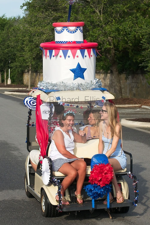 A family rides along in a golf cart decorated as a birthday cake during the annual Sullivan's Island Independence Day parade July 4, 2017 in Sullivan's Island, South Carolina. The tiny affluent sea island hosts a bicycle and golf cart parade through the historic village.