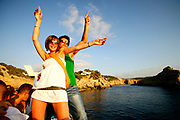 A glamourous, trendy couple dancing on a boat party, Ibiza 2005