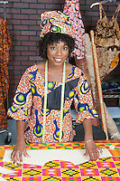 Portrait of an African American female fashion designer with sewing pattern and cloth