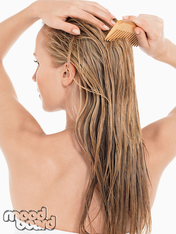 Young Blond Woman Combing wet Hair back view