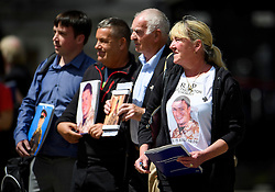 © Licensed to London News Pictures. 06/07/2016. London, UK. Relatives of servicemen killed in the Iraq war, hold up pictures of their relatives and copies of the Chilcot report outside the QE2 conference centre in London where the long-awaited Chilcot inquiry into the war in Iraq has been released. Photo credit: Ben Cawthra/LNP