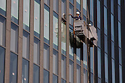 Window washers in a cradle high on the side of a tall office building in Tokyo, Japan. Thursday, October 15th 2009