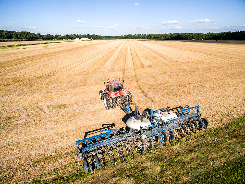 Aerial view of a planter moving through a field to double crop soy beans over wheat stubble on a local Maryland farm.