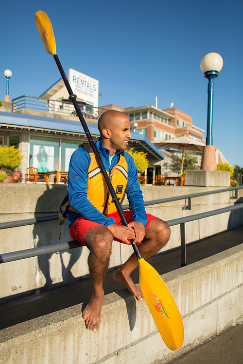 United States, Washington, Kirkland, man with kayak paddle at Carillon Point Marina.  MR