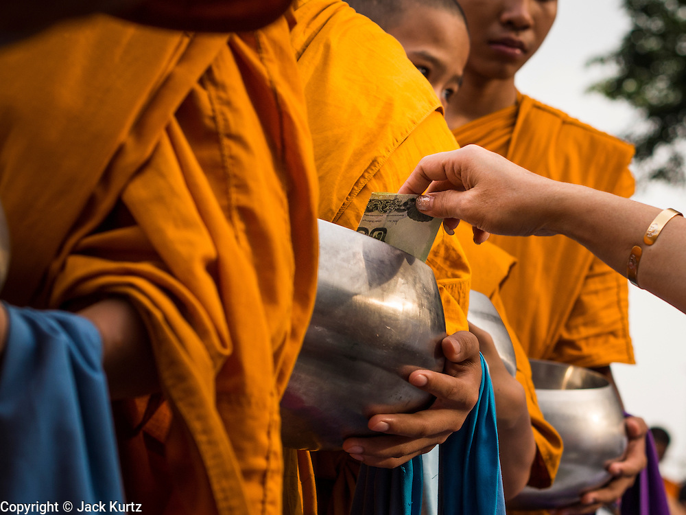08 SEPTEMBER 2013 - BANGKOK, THAILAND:  A person drops a donation into the alms bowl of a Buddhist monk during a mass alms giving ceremony in Bangkok Sunday. 10,000 Buddhist monks participated in a mass alms giving ceremony on Rajadamri Road in front of Central World shopping mall in Bangkok. The alms giving was to benefit disaster victims in Thailand and assist Buddhist temples in the insurgency wracked southern provinces of Thailand.     PHOTO BY JACK KURTZ