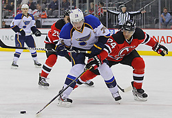 Feb 9; Newark, NJ, USA; New Jersey Devils defenseman Bryce Salvador (24) pokes the puck away from St. Louis Blues center T.J. Oshie (74) during the first period at the Prudential Center.