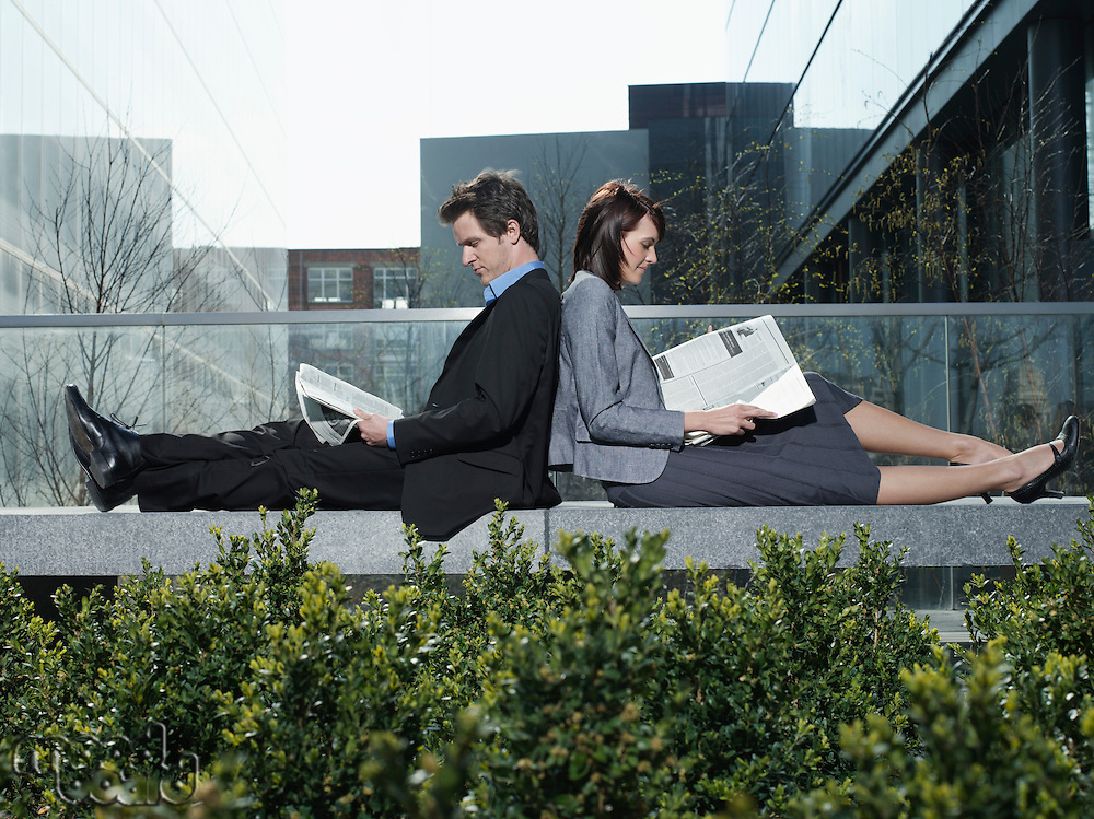 Business man and woman sitting back to back on wall outdoors reading newspapers side view