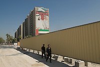 Two men walking under the portrait of Sheikh al Zayed along Sheikh al-Zayed road. Dubai, one of the seven emirates and the most populous of the United Arab Emirates sits on the southern coast of the Persian gulf.