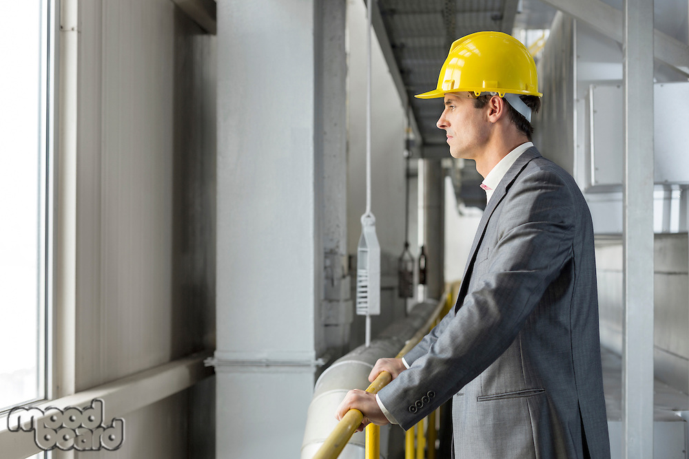Side view of thoughtful male architect standing by railing in industry