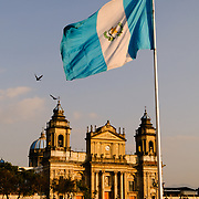 A large Guatemalan flag flies in the plaza in front of the Catedral Metropolitana (Metropolitan Cathedral) on the eastern end of Parque Central (officially the Plaza de la Constitucion) in the center of Guatemala City, Guatemala.