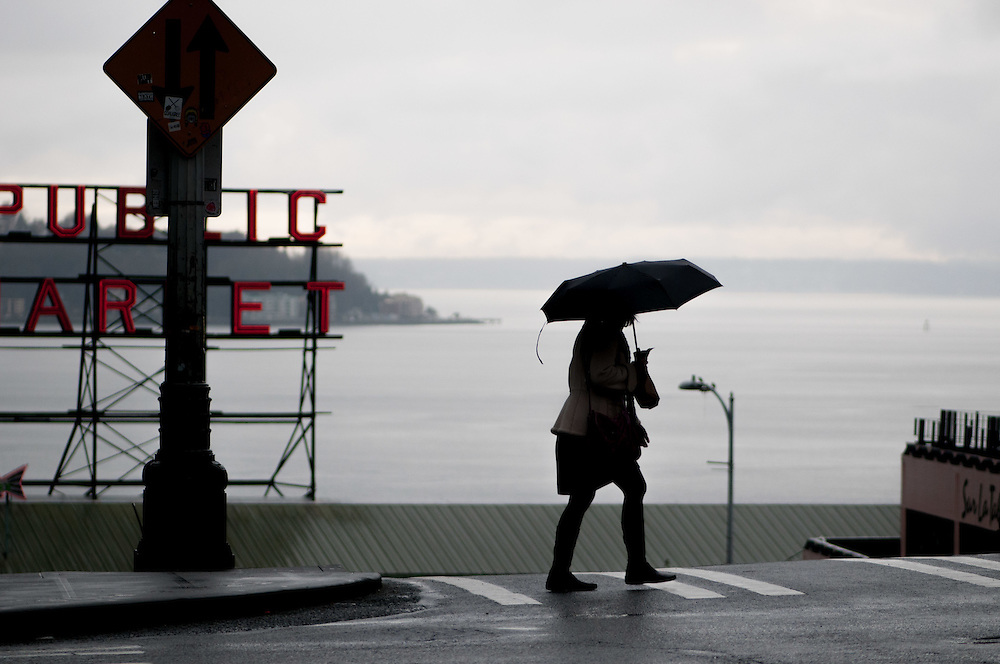 A lady walks across the street on a rainy day in Seattle