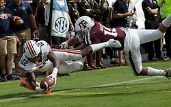 Auburn wide receiver Eli Stove (12) dives for the end zone for a touchdown as Texas A&M linebacker Anthony Hines III (19) defends during the fourth quarter of an NCAA college football game on Saturday, Nov. 4, 2017, in College Station, Texas. (AP Photo/Sam Craft)
