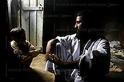 Shah Mohammad talks with his younger brother in his kitchen in Dir, Pakistan on Saturday Aug. 5, 2006. Shah Mohammad is a Pakistani who was captured in northern Afghanistan in November 2001 and later handed over to American soldiers. He was taken to Guantanamo Bay in June 2002. He, and two other Pakistani prisoners, were released at the end of April after 46 months.