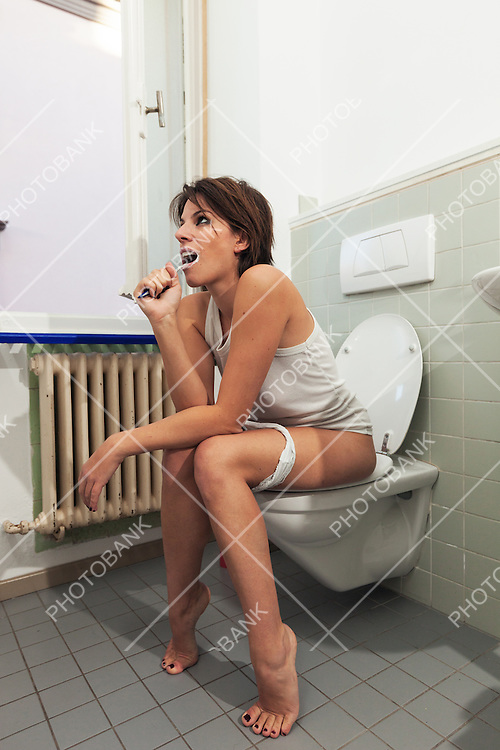 beautiful girl sitting on a toilet
