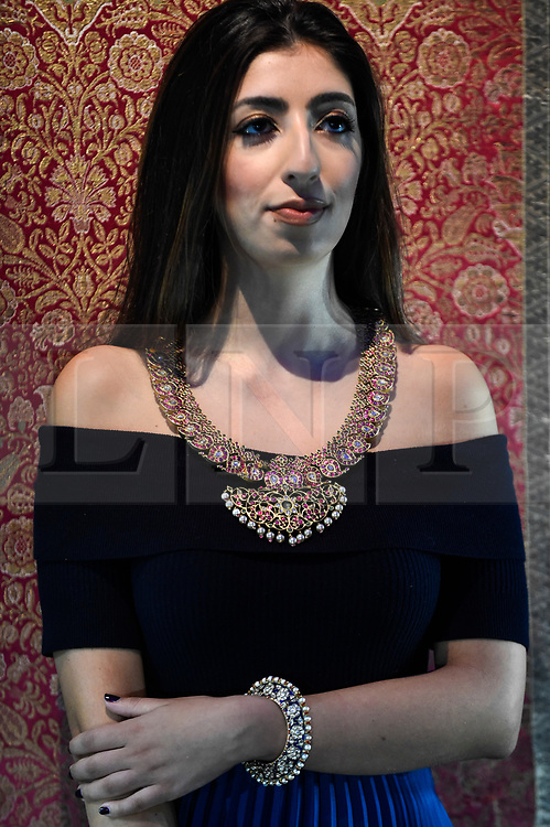 "© Licensed to London News Pictures. 18/10/2019. LONDON, UK. A staff member models ""A diamond, ruby, emerald-set gold Manga Malai necklace"", India, 19th century (Est. GBP40,000-60,000) and ""One of a pair of diamond-set and enamelled bracelets set with pearls"" North India, 18th century "" (Est. GBP15,000-25,000).  Preview of Islamic, Indian and Middle Eastern art to be auctioned at Sotheby's, New Bond Street, on 22 and 23 October.  Photo credit: Stephen Chung/LNP"