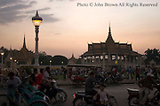 The Royal Palace stands as a backdrop to people gathered near the riverside promenade at sunset in Phnom Penh, Cambodia.