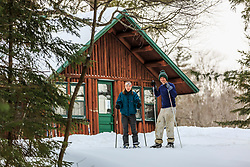 A couple on cross country skis outside Haskell Hut in Maine's Katahdin Woods and Waters National Monument.
