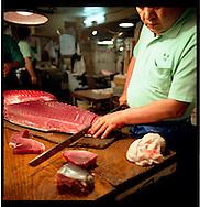 Cutting maguro (tuna) into steaks for later sale, Tsukiji Fish Market, Tokyo, Japan.