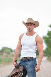 hot cowboy holding a saddle