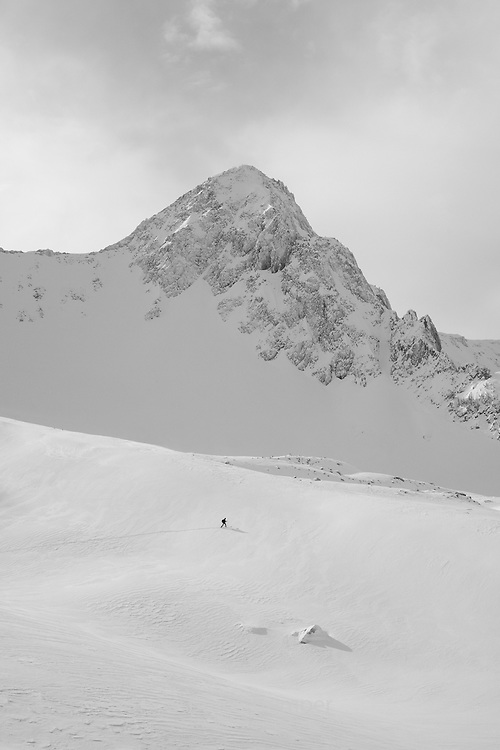 A backcountry skier in Maybird of Little Cottonwood Canyon, Utah with the Pfeifferhorn behind.