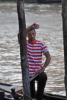 A handsome, red and white shirted gondolier in Venice, Italy.