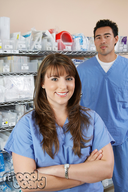 Female and male nurse standing by shelves with medical supply, portrait