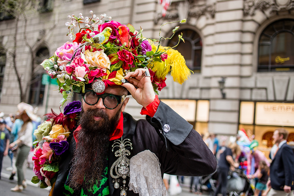 New York, NY - April 16, 2017. A man in an elaborate costume with a huge hat covered in flowers and birds  at New York's annual Easter Bonnet Parade and Festival on Fifth Avenue.
