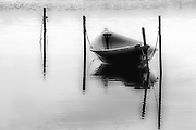 A small fishing boat is moored in the calm waters of Kaneohe Bay, Oahu, Hawaii. Black and white photographic art.
