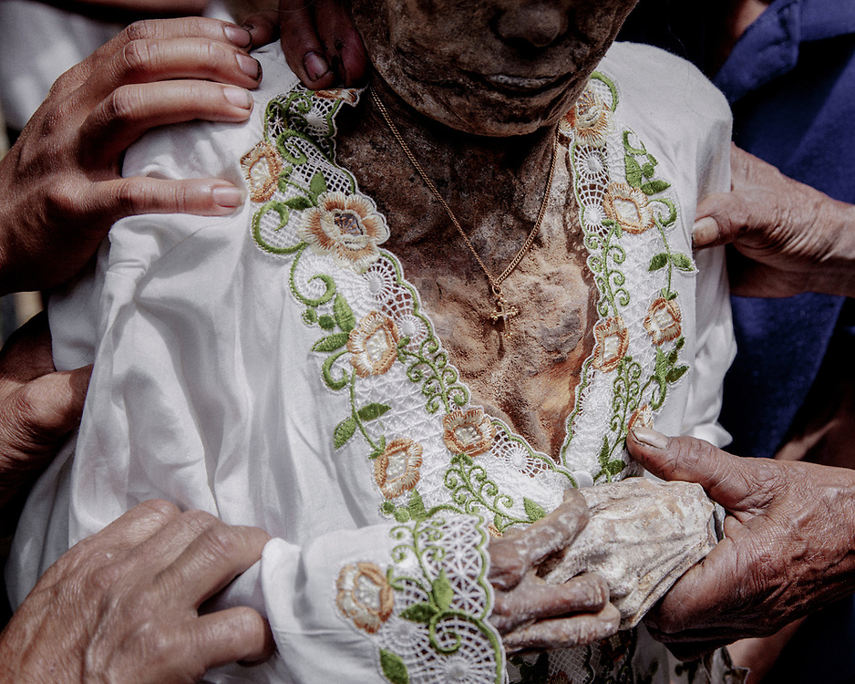 Tulak (55), Sattu's daughter, put on a new dress and a gold necklace before putting her body back into the coffin.<br /> <br /> Ma'nene is a tradition that takes place in August after harvest where the bodies of the dead loved ones are exhumed to be cleaned, groomed and dressed. For most, it's a bittersweet moment, a chance to reunite and physically see and touch and reconnect with loved ones who had passed on.